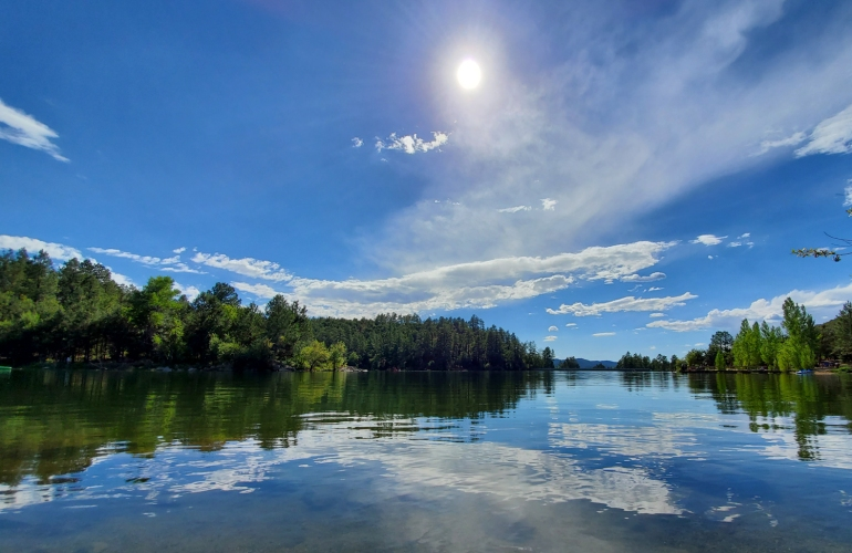 A lazy sun hangs over clean water and happy trees
